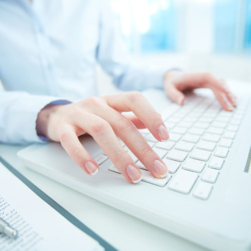Hands of white collar worker typing on laptop keypad